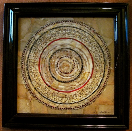 "Rondo Expansivo. Mosaic paper collage and ink asemic writing on framed mat board, finished with multiple coats polyurethane varnish. Hanger fixed on back. 11.25"" x 11.25"". $175.00."